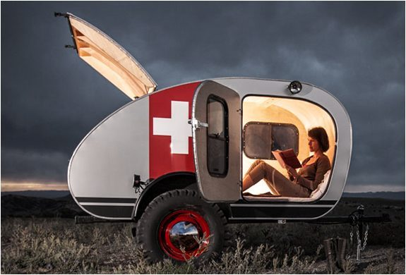 Best Teardrop Trailers - woman reading a book inside a brightly lit vintage overland trailer