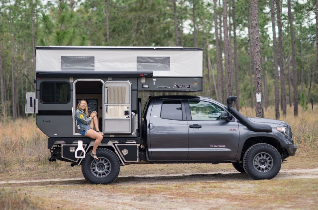 Man sitting in the side door of her Toyota Four Wheel Camper!