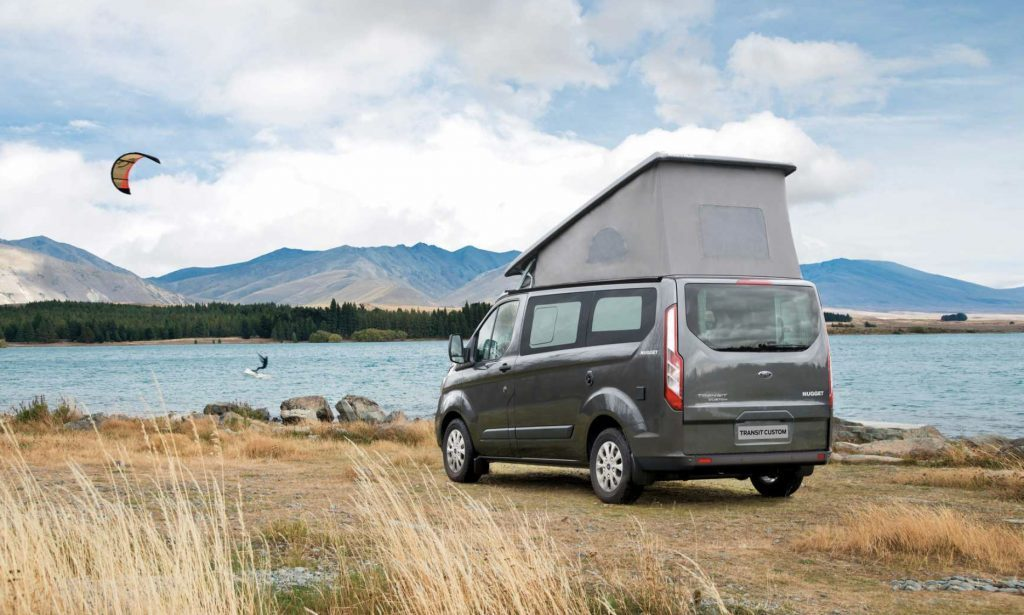 Ford Transit Nugget by a lake with the pop topped, and a kite-surfer in the background