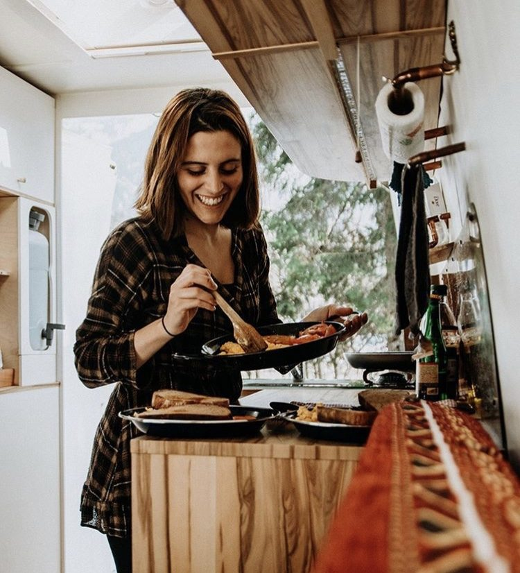 How to live off grid- woman cooking in a van.