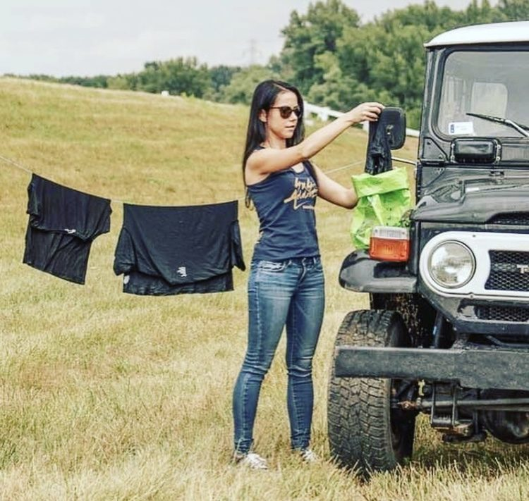 Woman hanging up washing from scrubba wash bag next to a Land Rover.