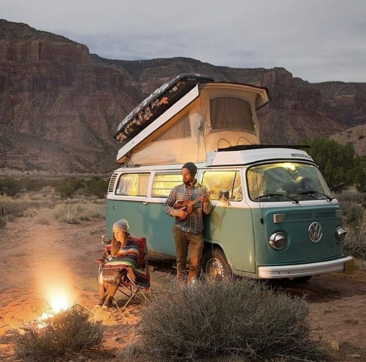 Campfire outside a blue VW bus.