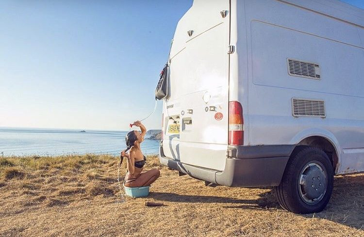 How to live off the grid- woman showering outside next to sprinter van.