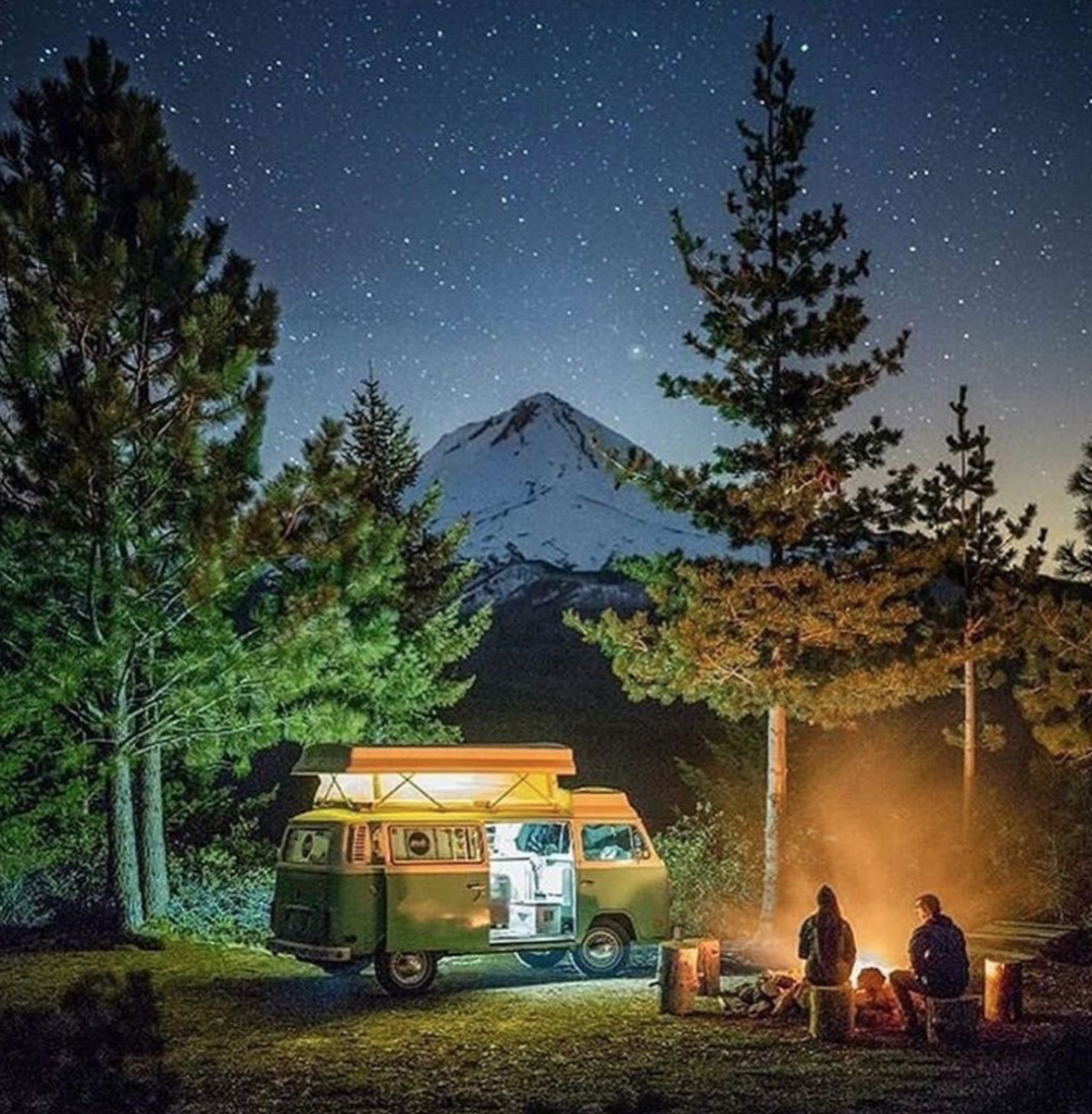 VW bus under the stars next to a camp fire