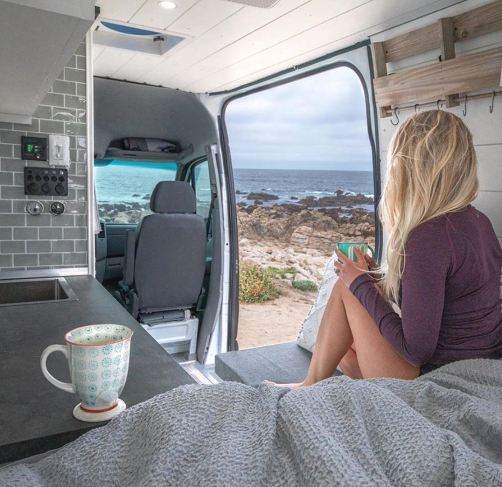 Girl looking out at the sea in her Off Grid Camper