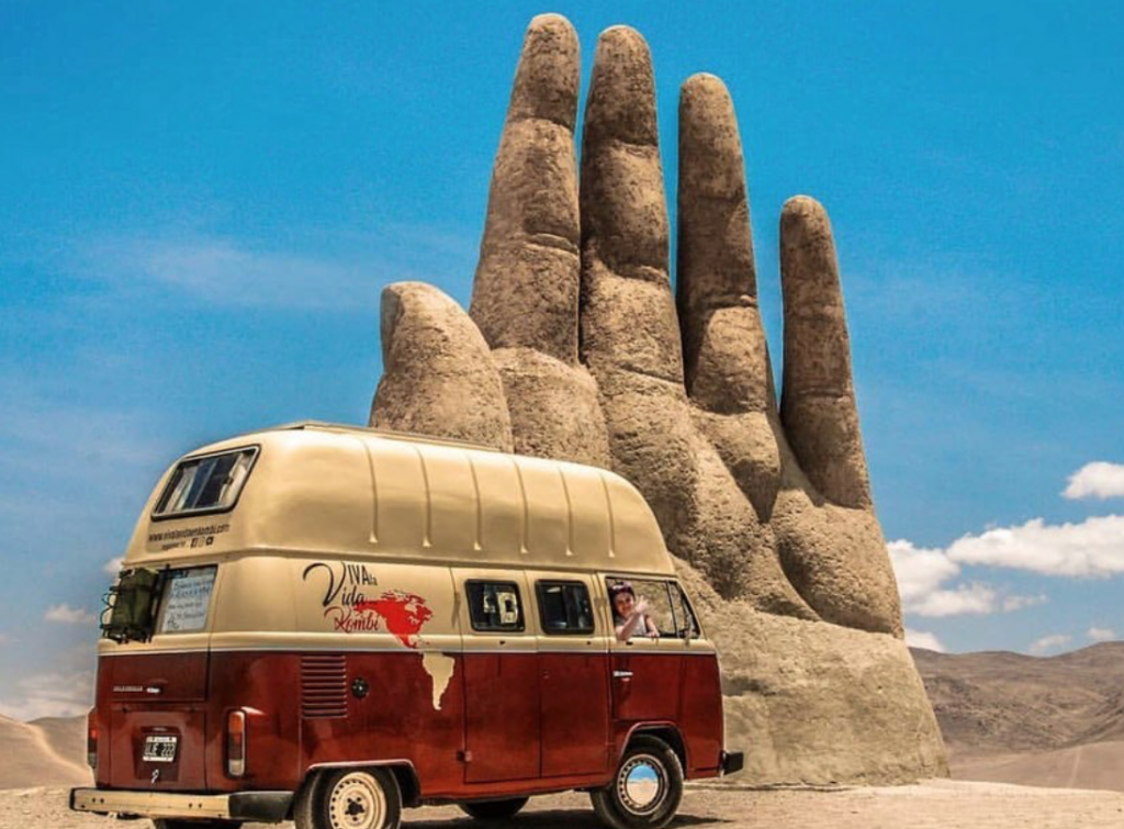 VW Bus next to a big hand carved from rock