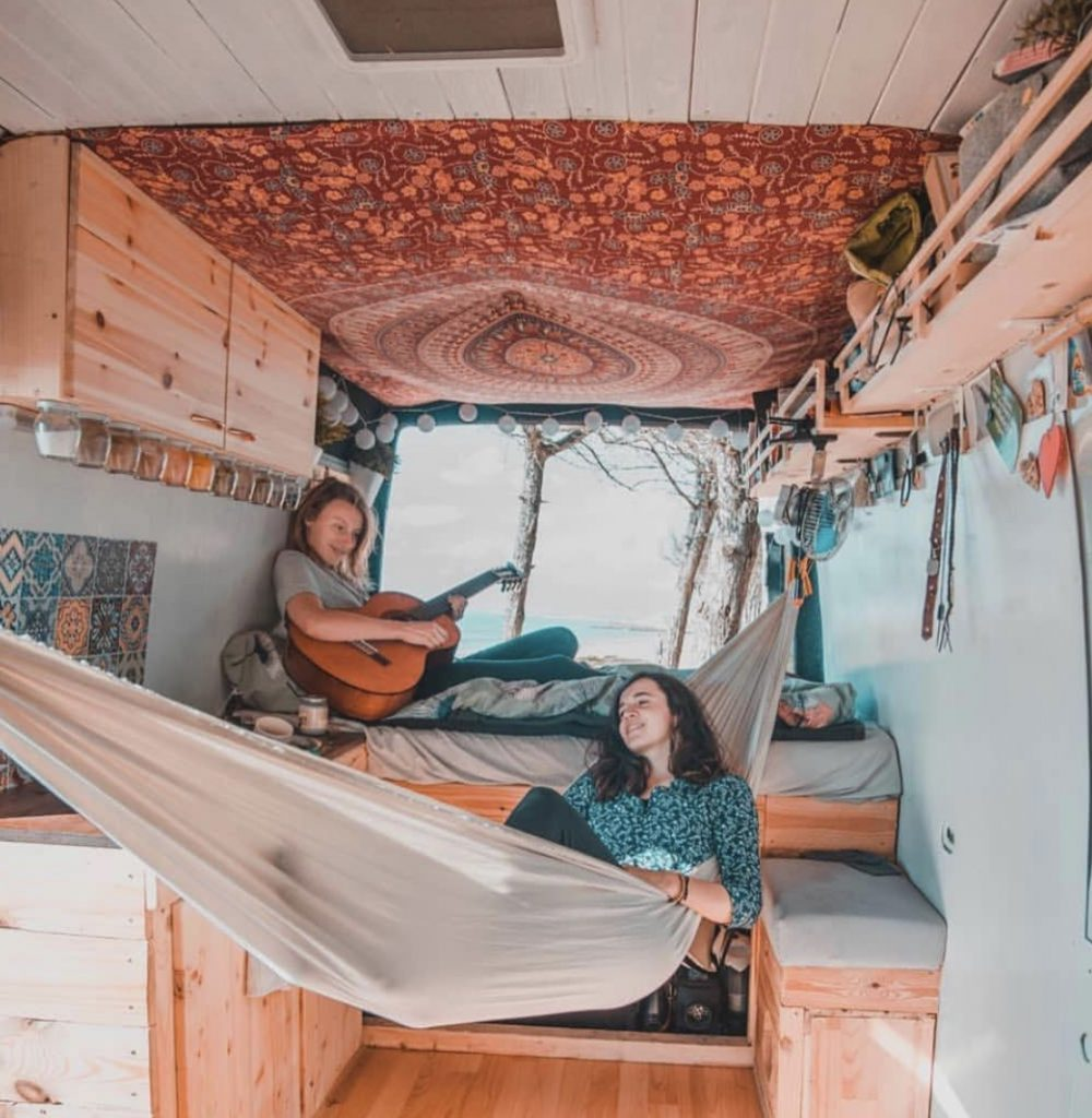 Couple in van, one in hammock, one on the bed with a guitar.