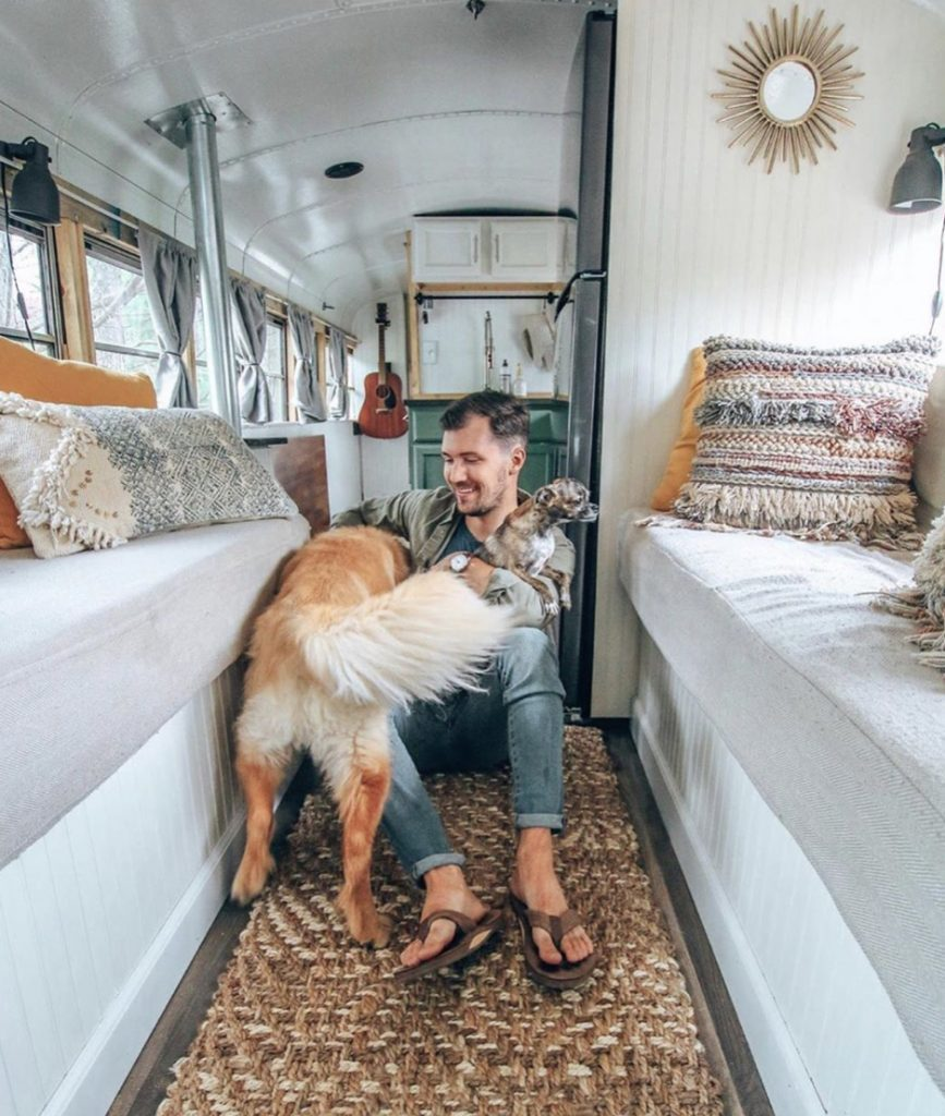 Man in converted bus with two dogs.