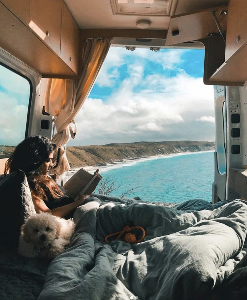 Woman sat in bed in her camper van with her dog, view of the ocean.