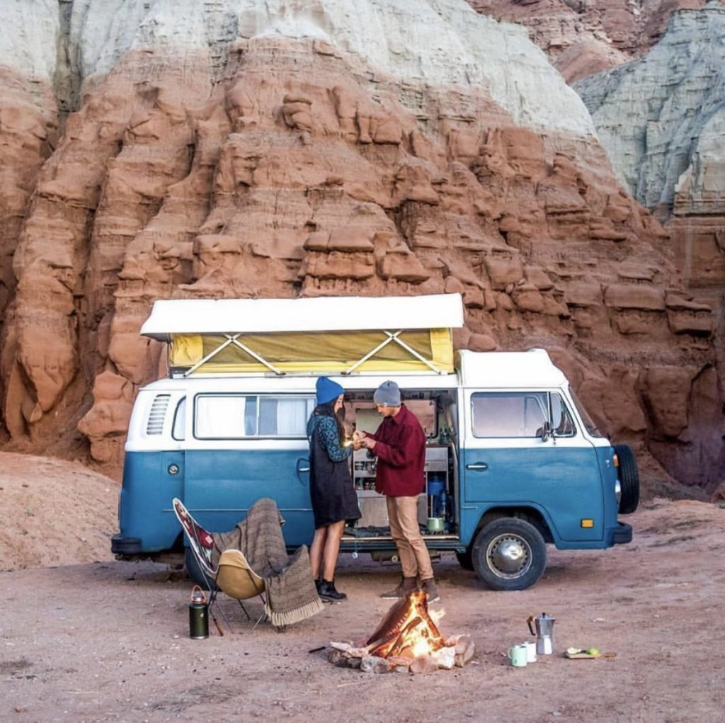 A couple out side their VW pop top in the desert.