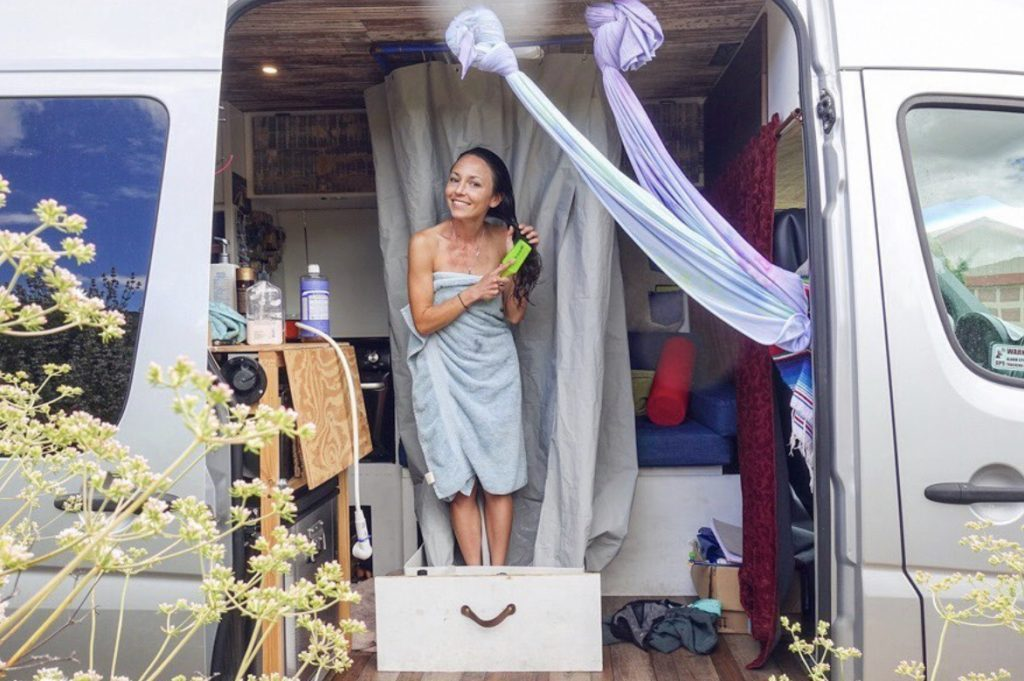 Woman showering in her sprinter van camper.