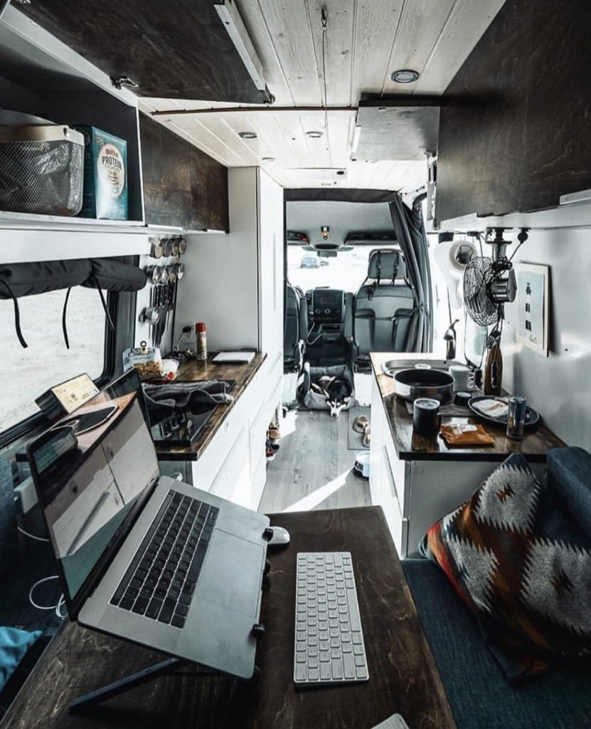 Work station with laptop inside camper van.