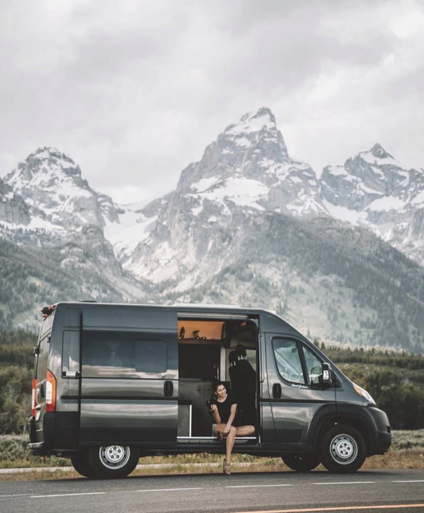 Women sat on the steps of her van in front of mountains.
