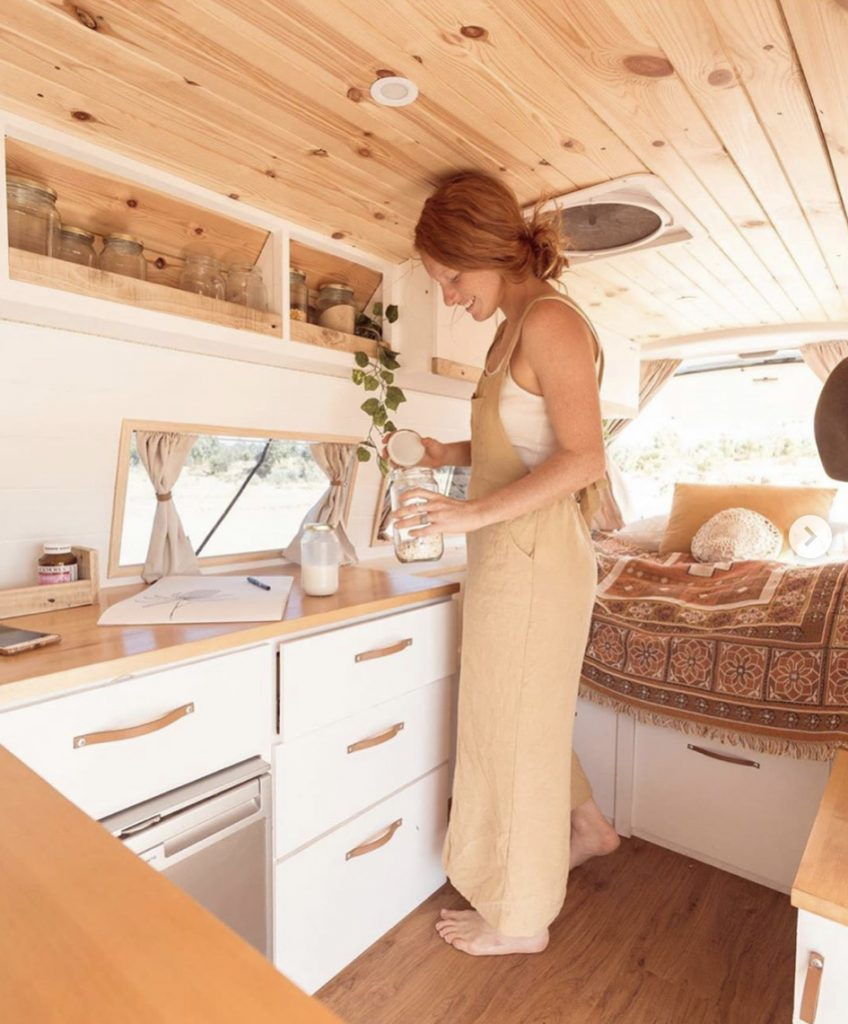 Woman making a drink in her camper van kitchen.