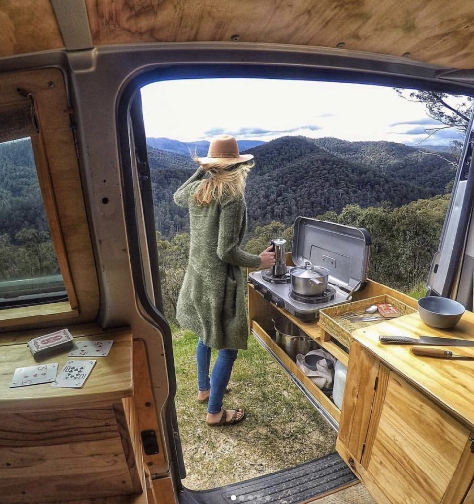 Woman cooking on slide out outdoor kitchen from her van.