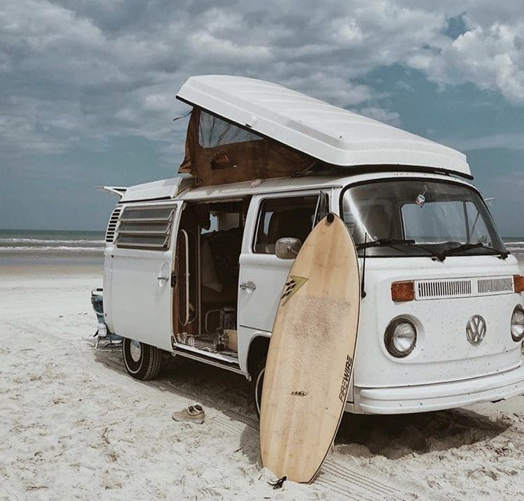 White VW pop top parked on beach with surf board