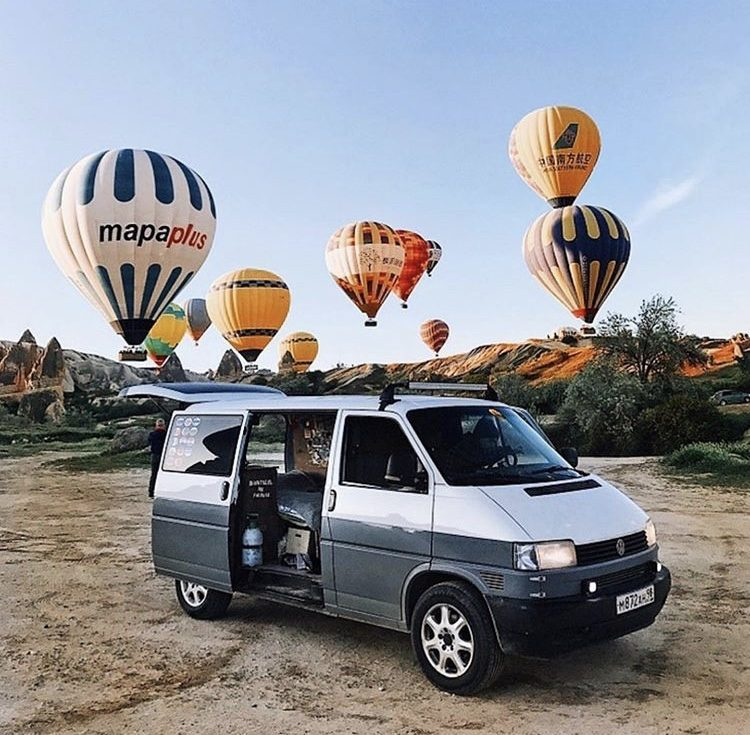 van parked infront of hot air baloons taking off