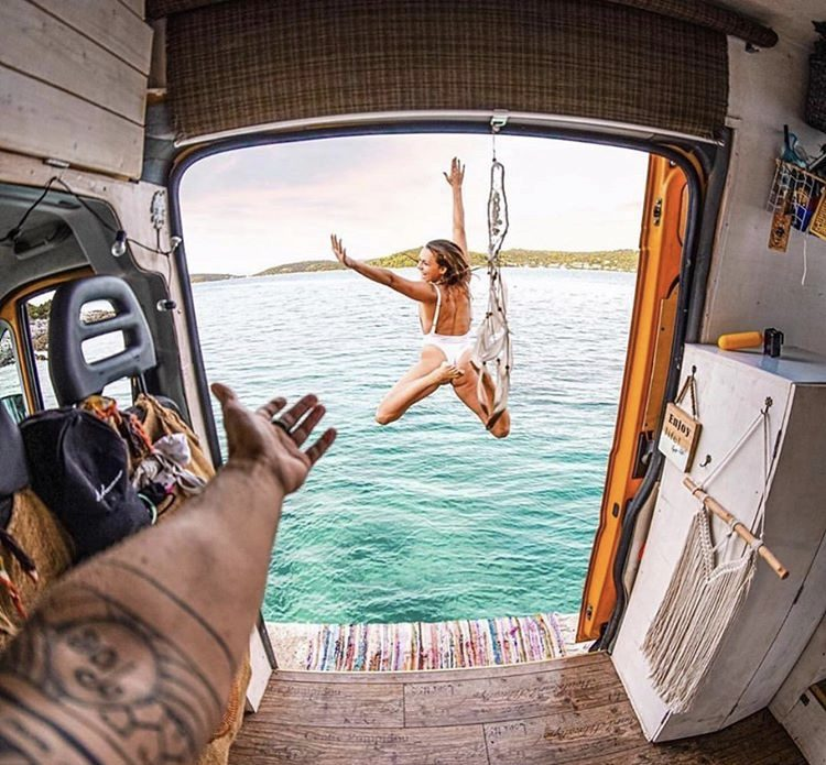 camper life - woman jumping oiut of van and into water