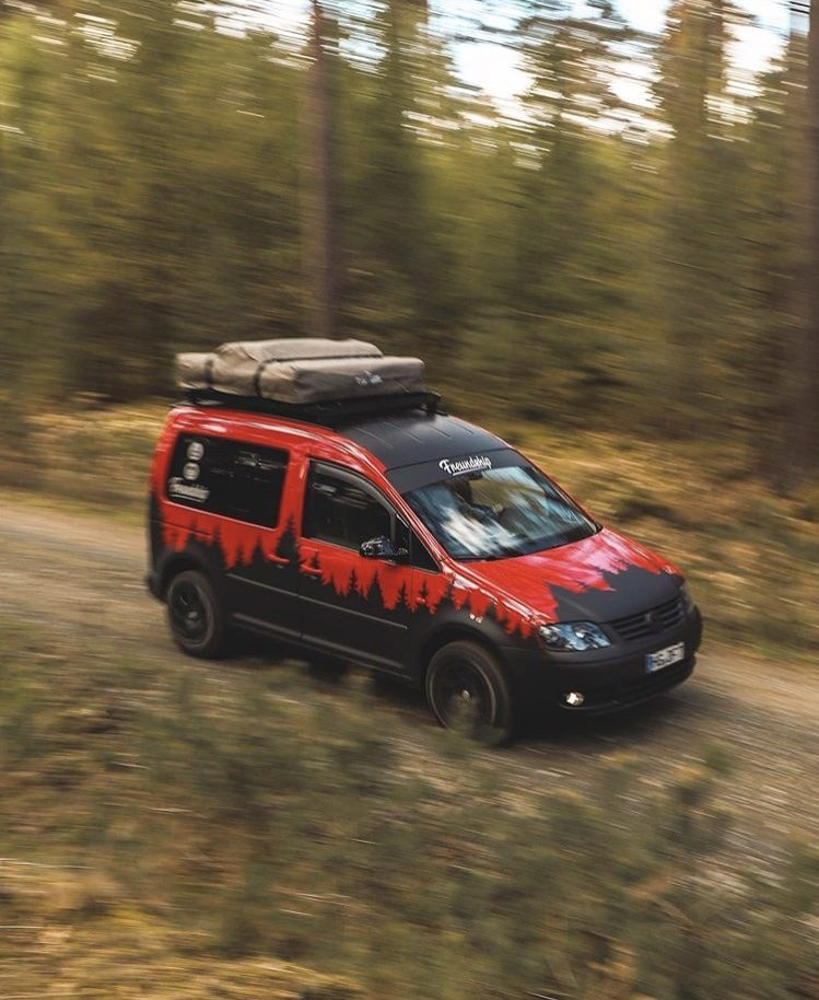 Red VW Caddy Camper speeding through forest with blurry trees.