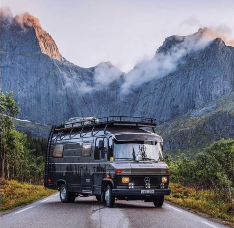 camper parked in front of mountains