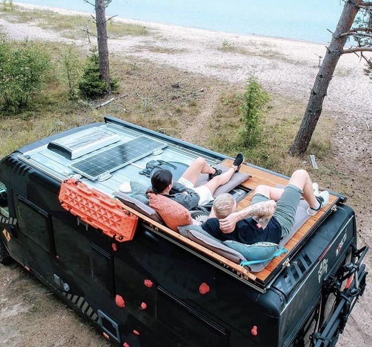 couple sat on top of camper looking at ocean