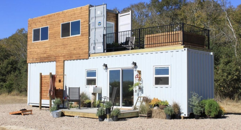 Shipping container homes exterior, grey shipping container on bottom, smaller cladded container on top.