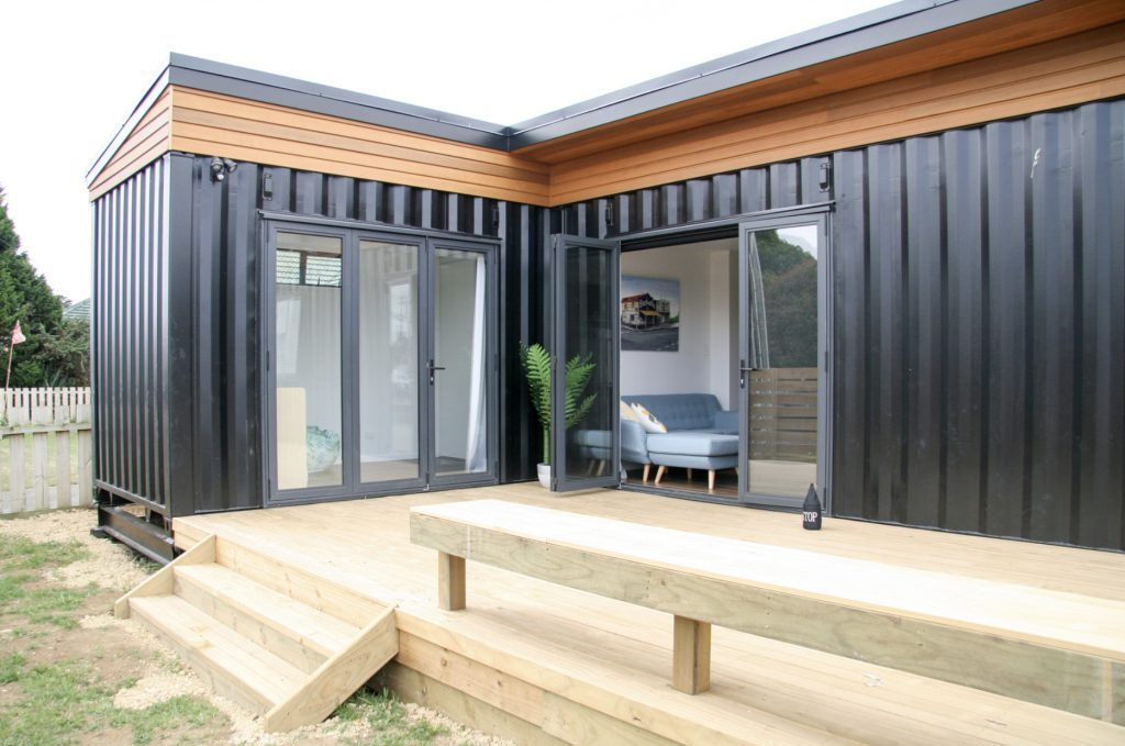 Shipping container homes - black L-shaped shipping container house.
