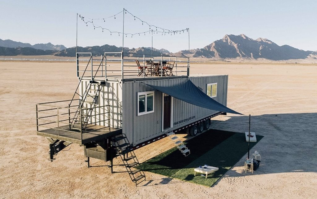 Shipping container home in the desert, on stilts.
