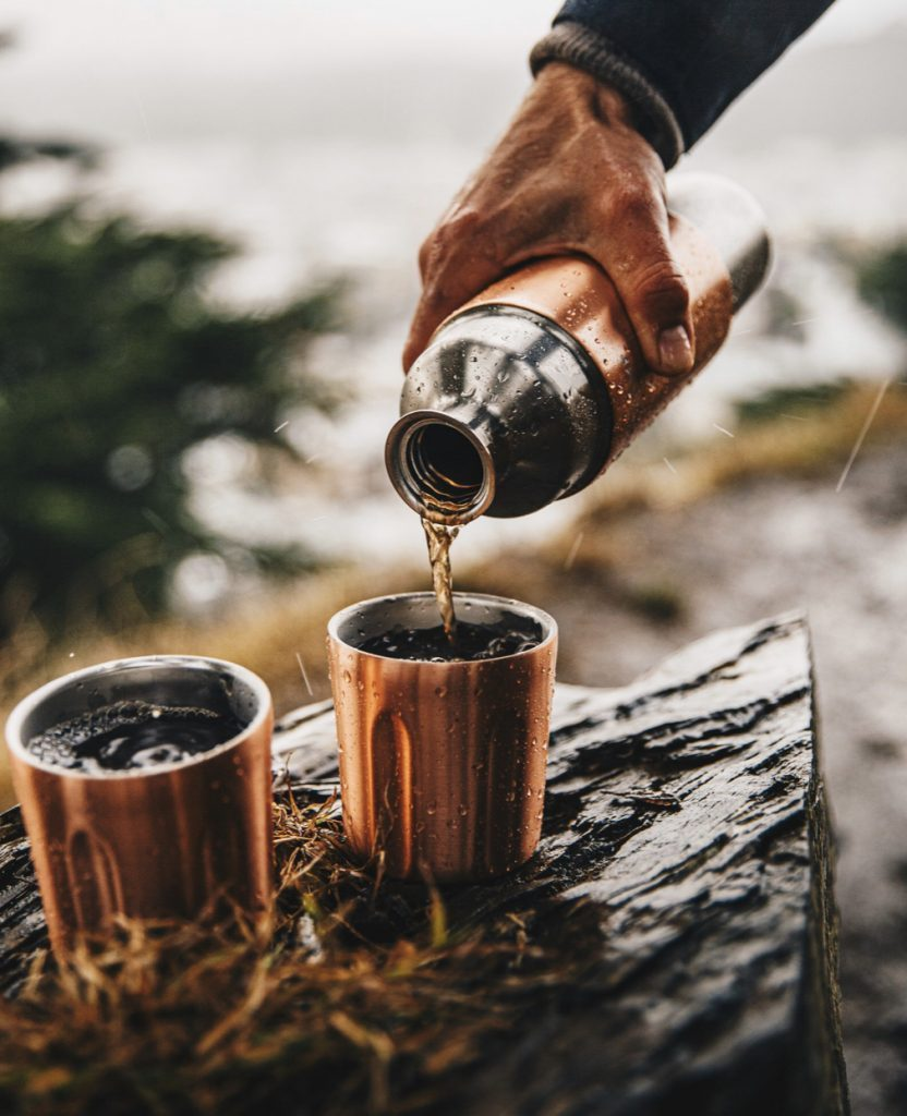 Pouring a dink into tumblers from the High Camp Flask