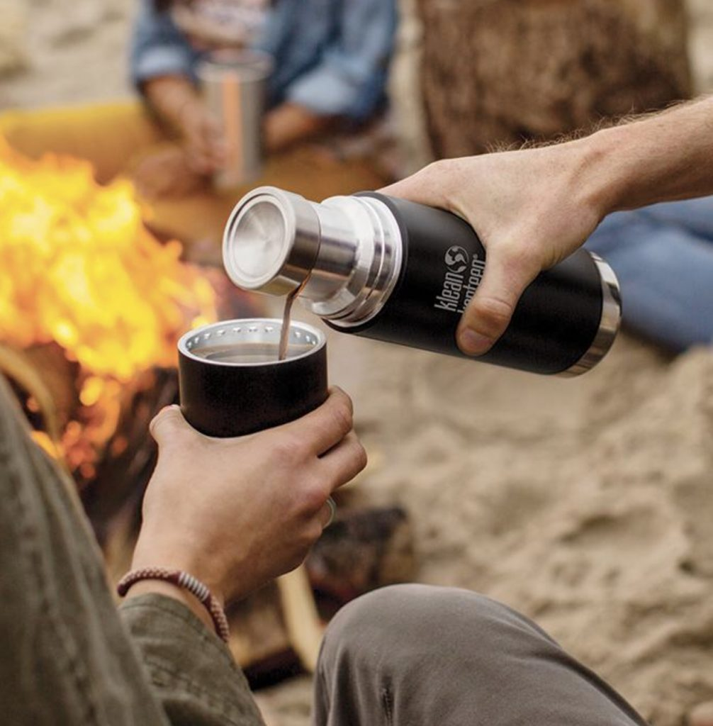 Pouring a drink from a Klean Kanteen by fireside