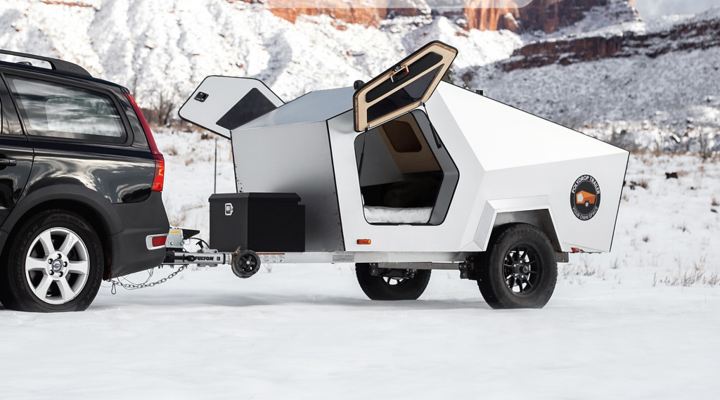 Best teardrop campers - The Polydrop Trailer being pulled by a standard saloon car. Its Delorian style doors are open, and this camper utilises lots of straight lines and geometric design elements