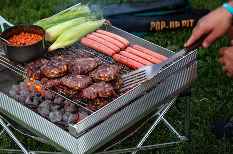 best trailer accessories - a large fire pit with a selection of meat and beans cooking on the top.