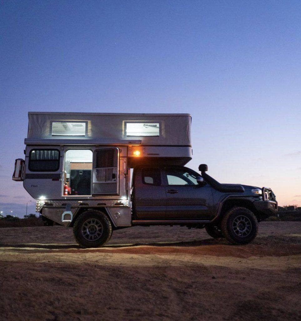 Best Motorhomes - Four Wheel Camper at night with roof popped