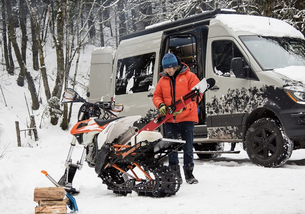Timber Den by Outside Van exterior in the snow with snowmobile in front