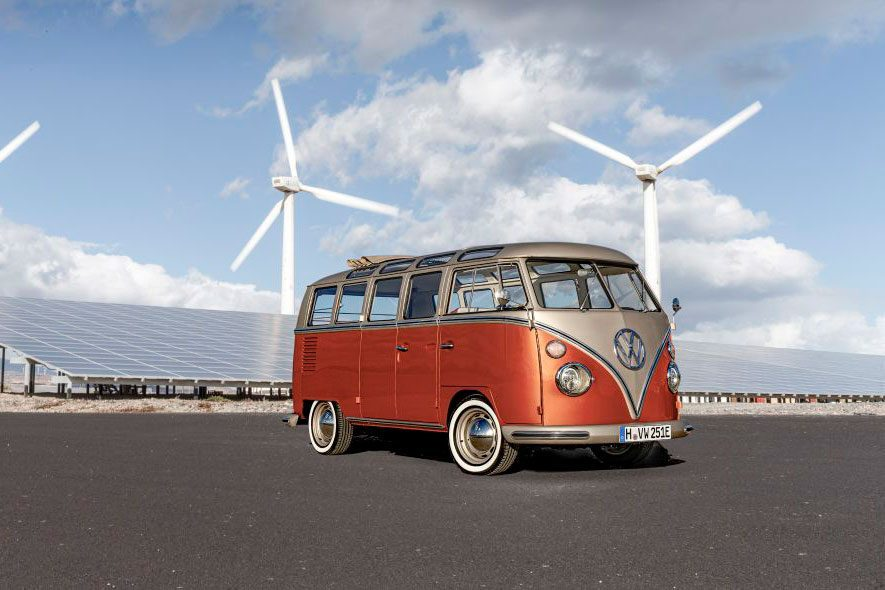 electric microbus with wind turbines in the background