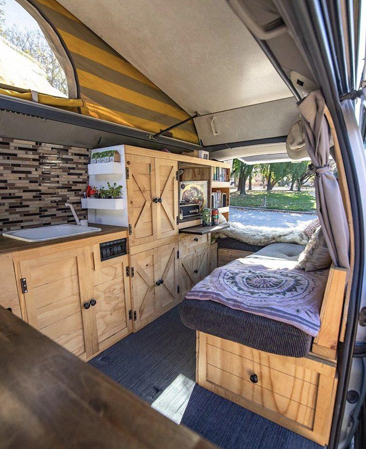 Custom van ideas- wooden cabinetry and bench seat inside van with pop top open.