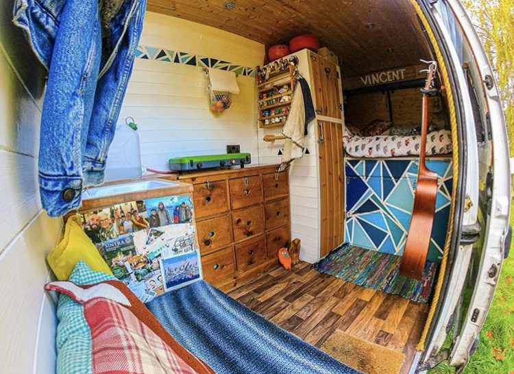 Van interior with wooden and white walls and funky pattern on drawers beneath fixed bed at back.