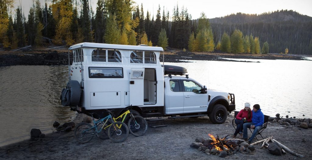 Best RVs- EarthCruiser EXD exterior with roof popped, infront of lake with campfire and people sat around