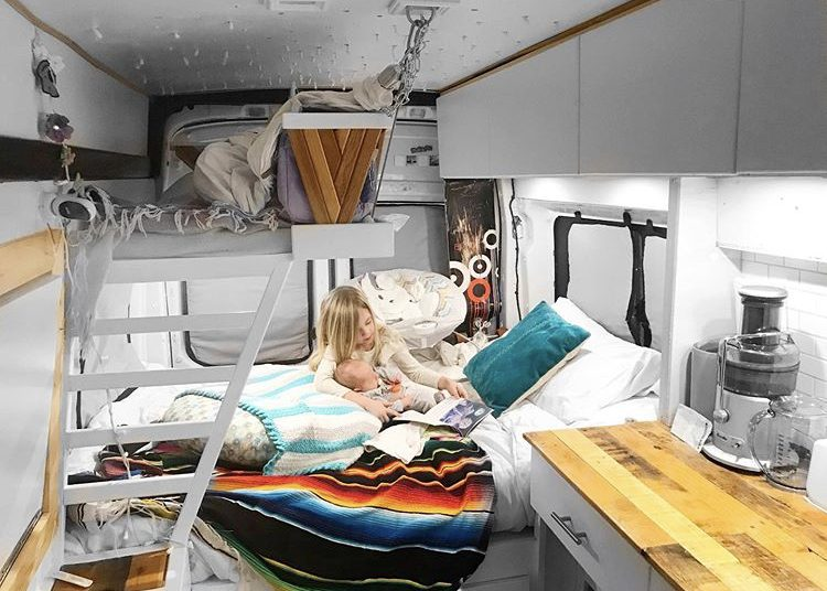 Custom van ideas - inside of bed with static bed at back and bunk bed above for kid. Kid holing baby on bed reading books.