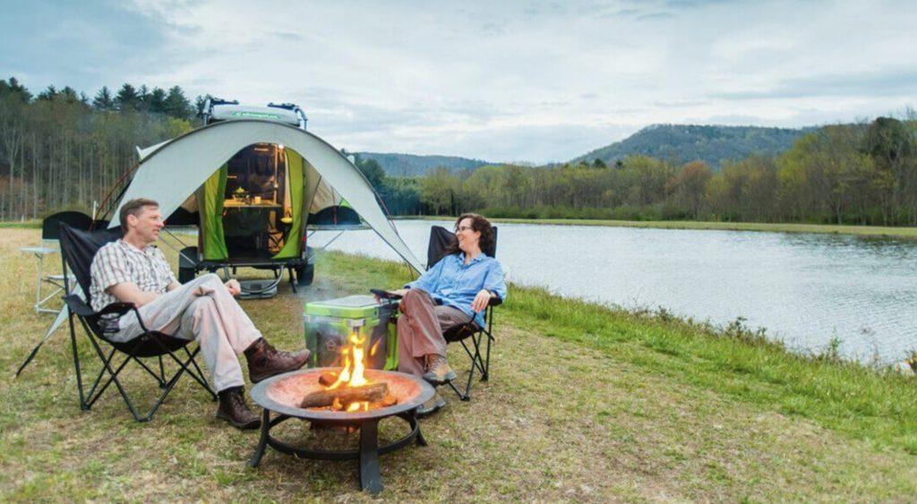 Small pop up campers - exterior of camper with people sat outside round fire.