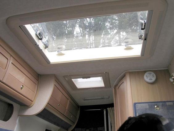 camper van windows - a large skylight with a view of trees above
