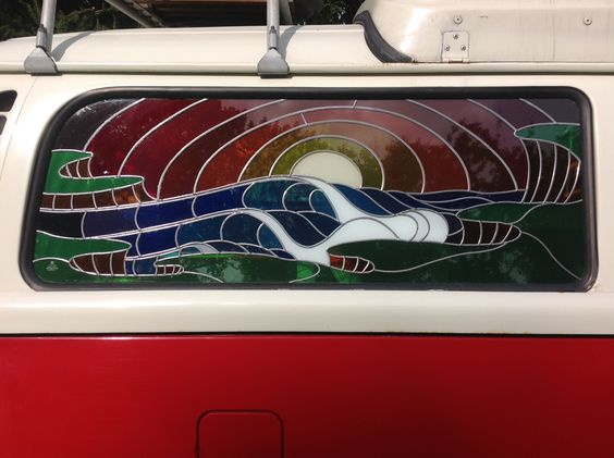 Stained glass window in a VW camper. The image is of a sunset