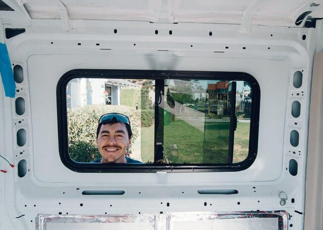 camper van windows - a happy guy fitting a window in the side of his van