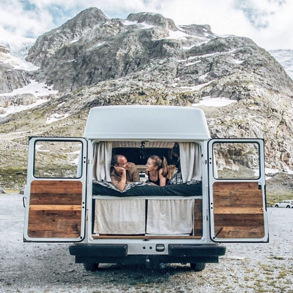 Two people in a van infront of a mountain