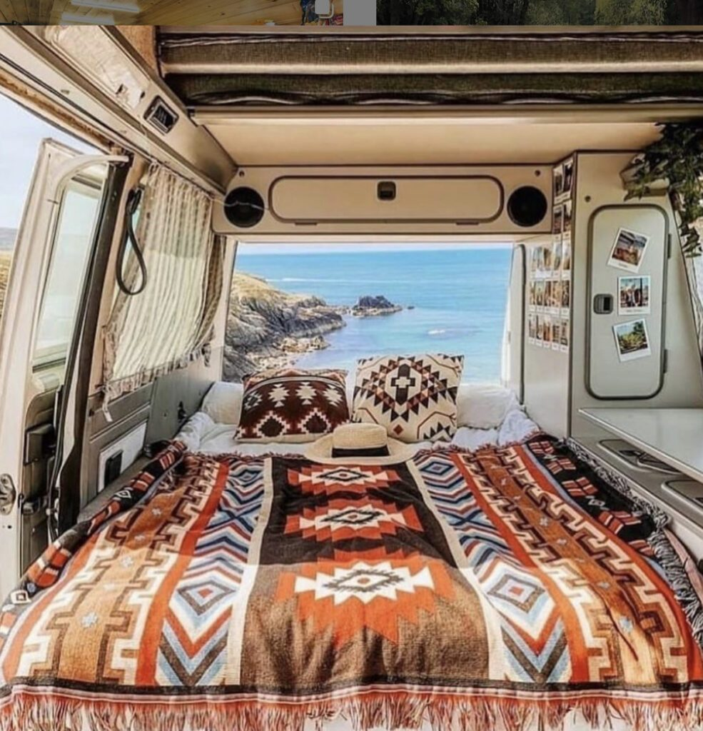 Camper mattress - bed with colourful blanket in van and sea view