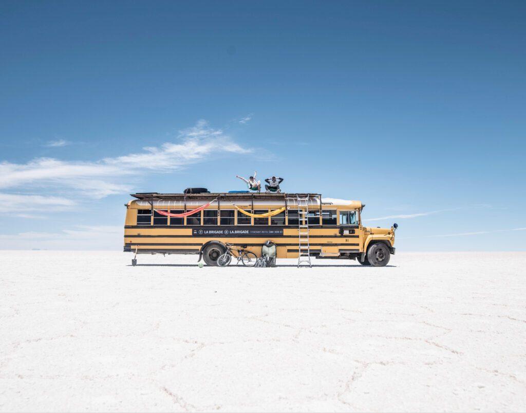 School bus camper - skoolie on salt planes with two people sat on top