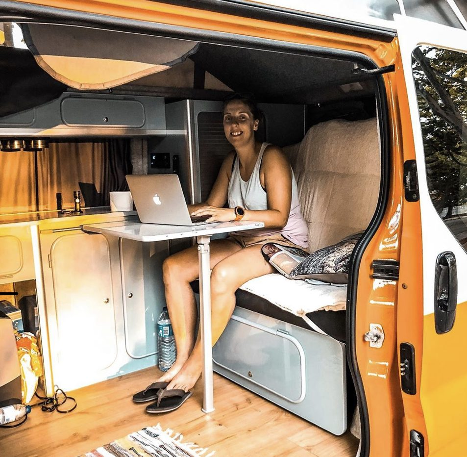 Woman working at a laptop inside her van