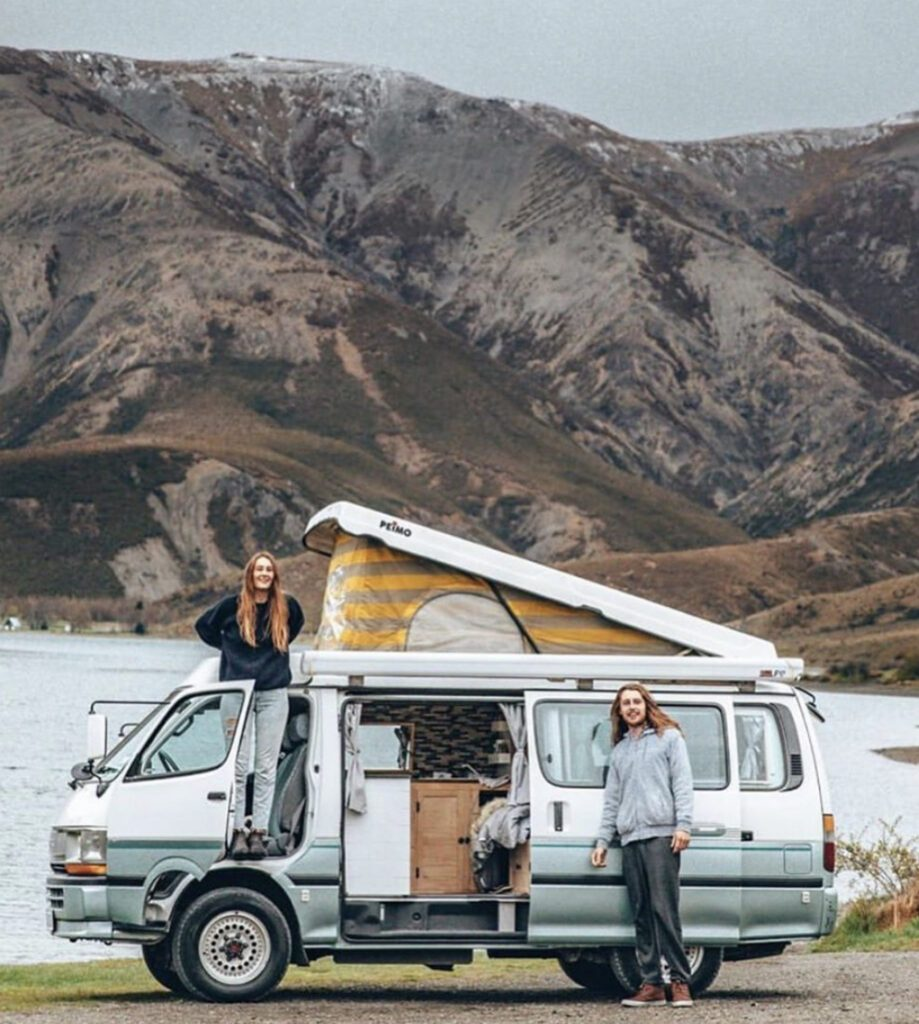 Pop top camper with roof up infront of lake and mountains