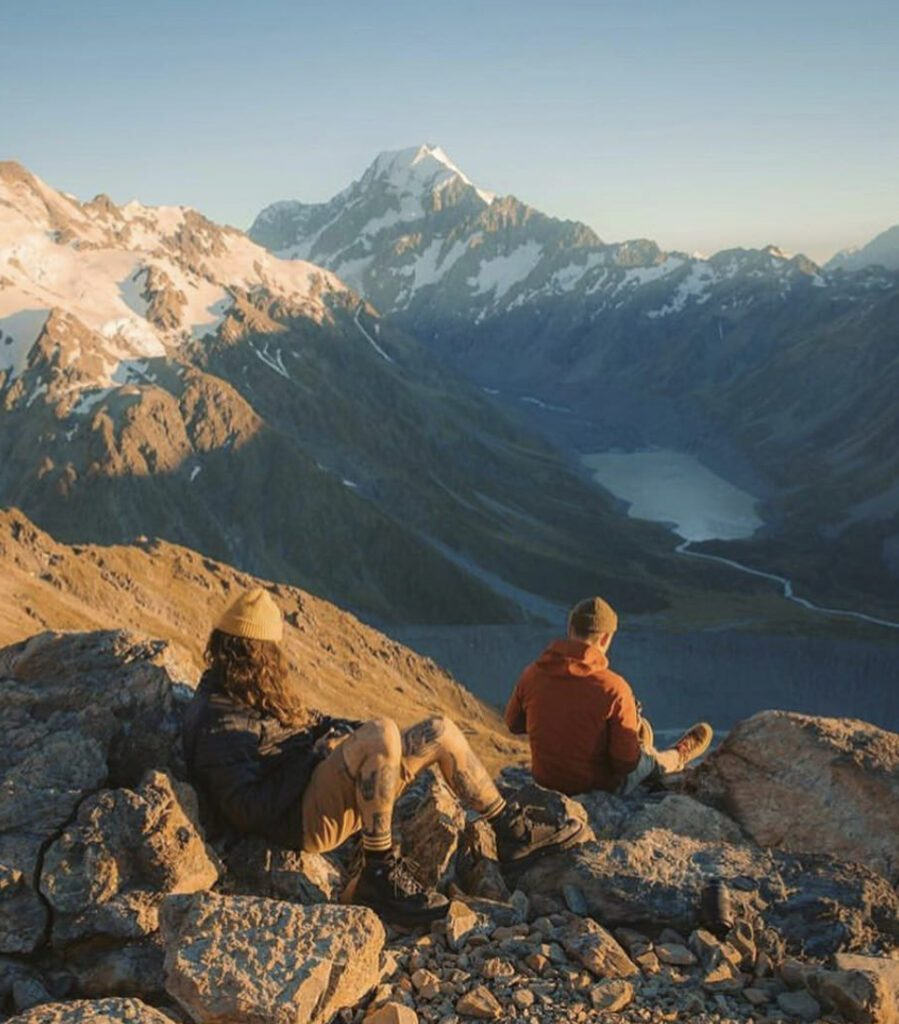 Two men sat in shorts and hats on mountain