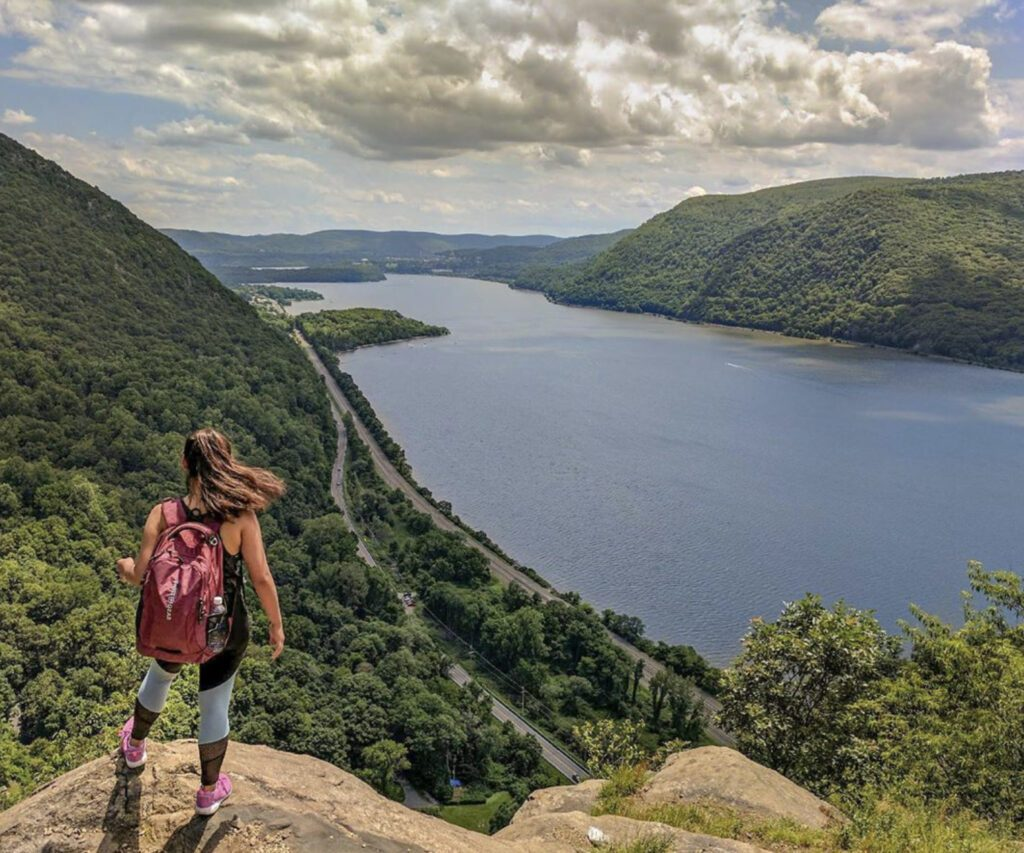 What to bring on a hike : woman overlooking lake and trees on hike